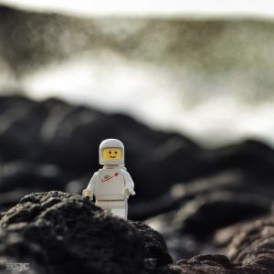 classic lego white space man walks across the lava bed at Pu'uhonia O Honaunau while the waves crash behind him in a wall of white spray